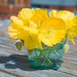 Welsh poppy (meconopsis cambrica) in shallow blue glass;on old garden table — Stock Photo #8956931