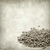 Textured old paper background with brown lentils — Стоковое фото