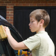 Cute little serious boy washing black car outside in siunshine — Stock Photo