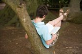 Summer reading - dark haired caucasian teenage boy reading a book sitting on a big tree branch — Stock Photo