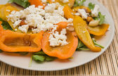 Summer light meal -- fried sweet pepper with garlic and crumbled feta cheese, on a bed of rocked salad — Stock Photo
