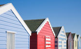 Row of colorful beach huts under blue sky — Stock Photo