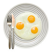 Three fried unbroken eggs on white plate with black stipe; fork and knife on the left, shot from the top; isolated; — Stock Photo