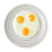 Three fried unbroken eggs on white plate with black stipe, shot from the top — Stock Photo