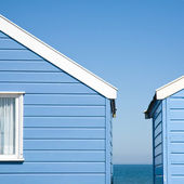Two blue beach huts under blue sky — Stock Photo