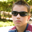 little caucasian boy in dark shades in sunny park — Stock Photo
