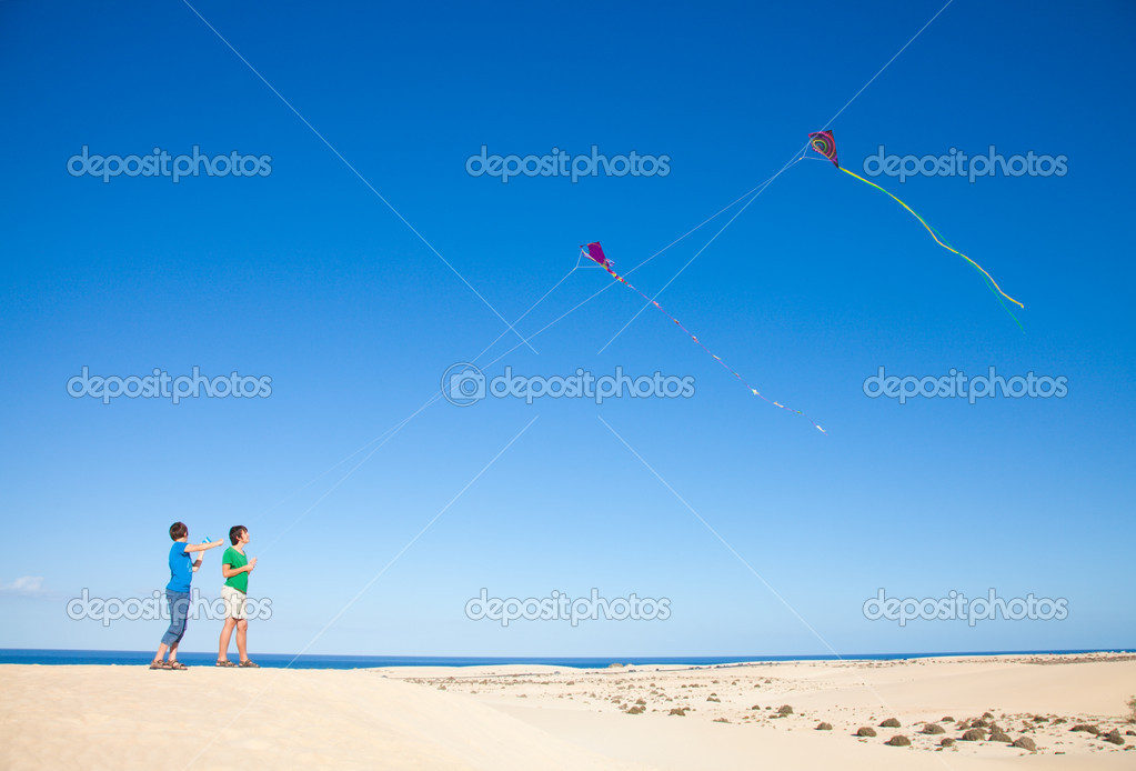 Two brothers are flying kites in natural reserve dunes of Corralejo, Fuerteventura, Canary Islands — Stock Photo #9920209