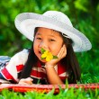 Young girl lying on a meadow with a hat on her head and a flower — Stock Photo