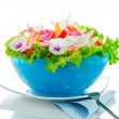 Fruit salad with edible flowers in a blue bowl from ice on white — Foto Stock