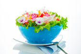 Fruit salad with edible flowers in a blue bowl from ice on white — Stock Photo