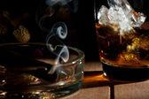 Ein glas whiskey mit einer zigarre rauchen in den aschenbecher — Stockfoto