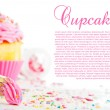 Cupcake and decorating bag on a white table with colorful sugar — Stock Photo #9109388