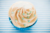 A cupcake in a blue baking cups with white cream, blue decoratio — Stock Photo