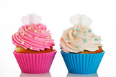 Two cupcakes in a pink and blue baking cups with pink and white — Stock Photo