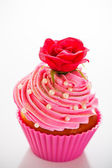 A cupcake in a pink baking cups with pink cream, white decoratio — Stock Photo
