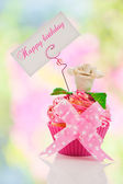A beautiful pink happy birthday cupcake with flower and a label — Stock Photo
