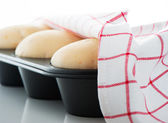 Yeast dough in a muffin pan with a white and red towel on white — Stok fotoğraf