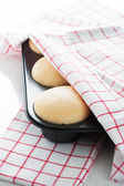 Yeast dough in a muffin pan with a white and red towel on white — Stock Photo
