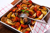 Chicken with vegetables on a baking tray as a studio shot — Stock Photo