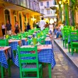 Typical greek taverna with tables outside on the street of Mediterranean Corfu town , street night scene - Stock Photo