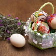 Stock Photo: Easter eggs in basket on wooden background