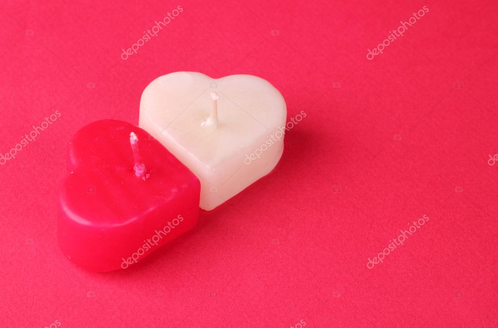 Image of heart shaped white and red candles bright red decorative cardboard background — Foto Stock #10151683