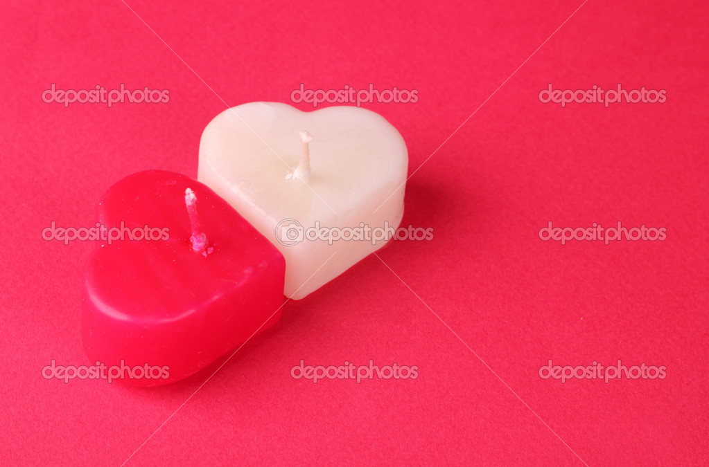 Image of heart shaped white and red candles bright red decorative cardboard background  Foto Stock #10151683