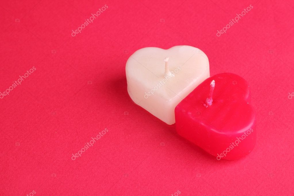 Heart shaped white and red candles bright red decorative cardboard background — Stock Photo #10151694