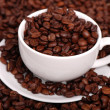 Stock Photo: Single white coffee cup over coffee background on coffee beans background