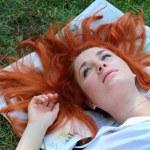 Beautiful young girl lying on the newspaper — Stock Photo