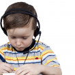 A little boy thinks the headphones with microphone — Stock Photo #9648146