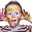 A happy little boy with a cute face smeared with paint — Stock Photo
