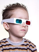 Cute little boy sitting in the 3D glasses — Stock Photo