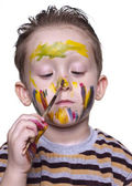 A little boy draws on the nose with a brush — Stock Photo