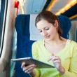 Young woman using her tablet computer while traveling by train — Stock Photo