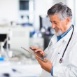 Senior doctor using his tablet computer at work — Stock Photo #10408052