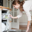 Housework: young woman putting dishes in the dishwasher — Stockfoto #10408381