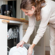 Housework: young woman putting dishes in the dishwasher — Stockfoto