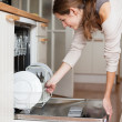 Housework: young woman putting dishes in the dishwasher — Stock fotografie