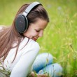 Portrait of a pretty young woman listening to music - Stock Photo