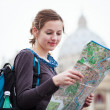 Pretty young female tourist studying a map — Stock Photo #10408497