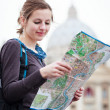 Pretty young female tourist studying a map — Stock Photo #10408502