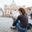 Pretty young female tourist studying a map — Stock Photo #10408503