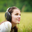 Portrait of a pretty young woman listening to music on her mp3 p — Stock Photo #10408507