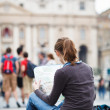 Pretty young female tourist studying a map — Stock Photo #10408567