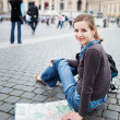 Pretty young female tourist studying a map — Stock Photo #10408572