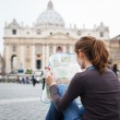 Pretty young female tourist studying a map — Stock Photo #10408578