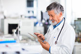 Senior doctor using his tablet computer at work — Stockfoto