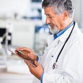 Ancien médecin à l'aide de son ordinateur tablette au travail — Photo