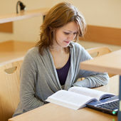 Pretty female college student in a llibrary (color toned image) — Stock Photo